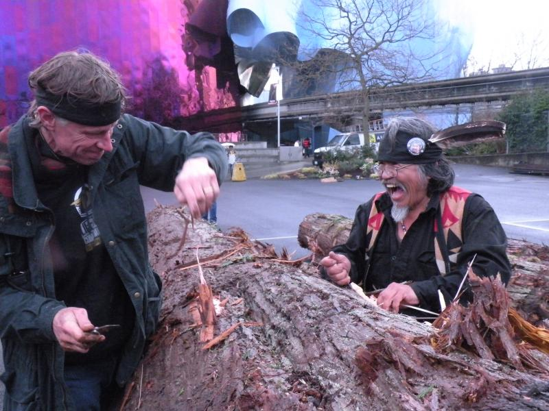 Late carver John T. Williams' brother, Rick, beams with joy as he and another carver, Dan Martin, make the first cuts on a 120-year-old cedar.  Their carve-in will go on for at least 6 months.
