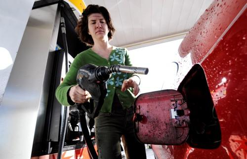 Jennifer Mendelson begins to fill her car's gas tank at a station near downtown Seattle.