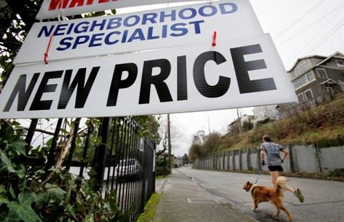 A jogger and dog run past a house posted with a new price in Seattle.