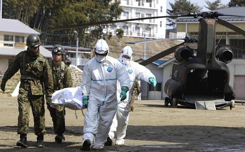 A resident suspected of being exposed to radiation is taken to medical care by a security team, in Nihonmatsu, Fukushima, northern Japan Sunday, March 13, 2011 following radiation emanation from a nuclear reactor after Friday's massive quake.
