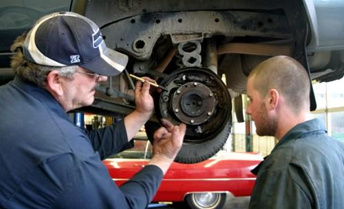 David Puki, left, helps inspect a drum brake with Hal Glade, at South Seattle Community College. Puki, a laid-off Boeing worker, is studying to be an auto mechanic.