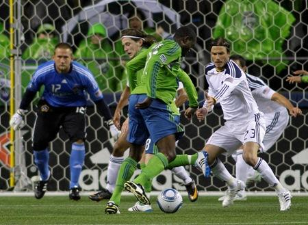 Los Angeles Galaxy's David Beckham defends as Seattle Sounders' O'Brian White looks for a shot and Galaxy goalkeeper Josh Saunders looks on during the 2011 season opener Tuesday, March 15, in Seattle.