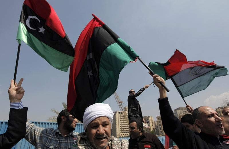 Flags of Libya's opposition, the pre-Gadhafi regime banner, are waved by opposition supporters on Tuesday in Cairo, Egypt, outside the Arab League meeting.