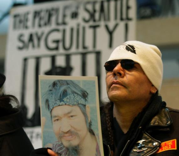 A protester named Redweezil holds up a photo of John T. Williams, a Native woodcarver killed by Seattle Police officer Ian Birk in August 2010. The killing sparked protests and was among the events prompting the ACLU to call for a federal investigation.