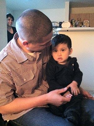 Alfonso Santos plays with his 1-year-old son Ezrah, as Ezrah's mother Kimberly Hernandez looks on from their kitchen in Caldwell, Idaho.