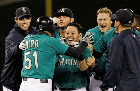 Seattle Mariners' Luis Rodriguez, center, is mobbed by teammates after hitting the game-winning runs in against the Toronto Blue Jays in the ninth inning Monday night's game at Safeco Field. Seattle. The Mariners won 8-7.