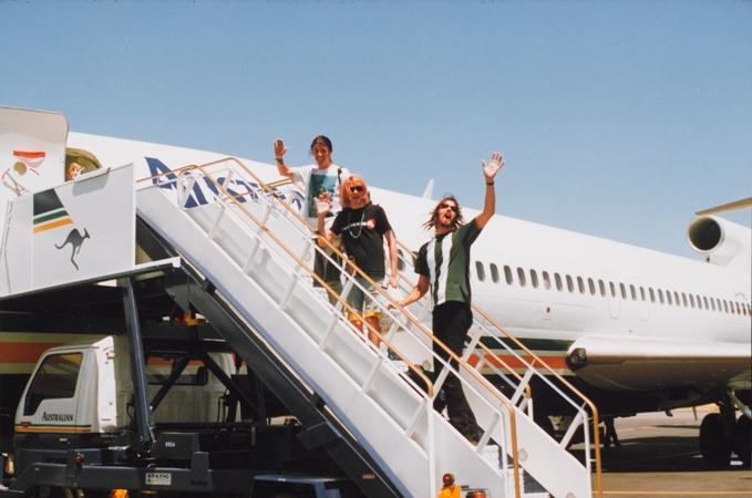 "Members of Nirvana (l to r: Dave Grohl, Kurt Cobain, Krist Novoselic) do their ""Beatles wave"" while boarding a flight out of Australia in 1992."