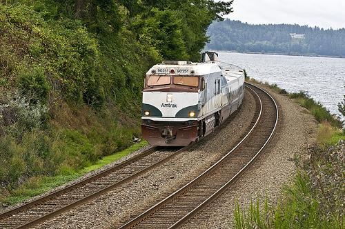 The Amtrak Cascades passenger train running along the bottom of a steep bluff near Steilacoom