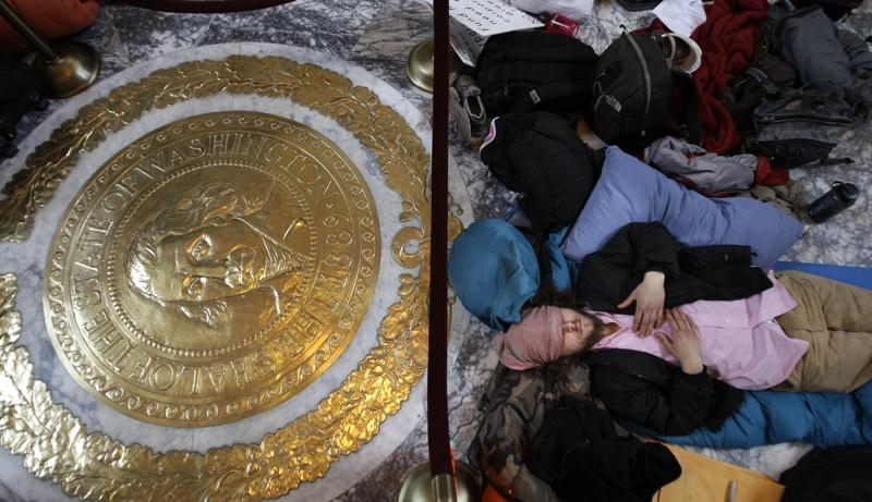 Caleb Hollatz, a protestor who spent the night in the Capitol in Olympia, Wash., sleeps on the floor of the rotunda near the state seal, Thurs., April 7, 2011. Several dozen protestors stayed overnight in the Capitol, and 17 were arrested.