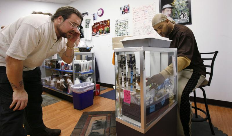 Robert Mangum, right, assists member Nate Murray in purchasing medical marijuana products at the Green Hope Patient Network, Tuesday, Dec. 14, 2010, in Shoreline, Wash.