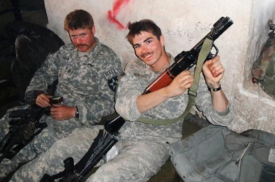 Jeremy Morlock, right, poses with Staff Sgt. David Bram with weapons that they have allegedly taken from dead Afghans.
