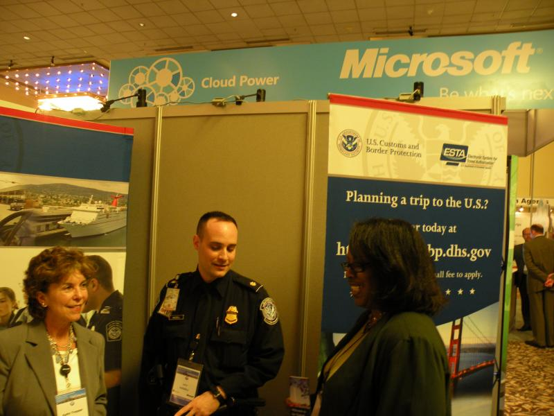 Kathi Trepper, John Hassell and Kelly Nance tending the Customs and Border Patrol booth inside the exhibition hall at the 2011 World Customs Organization IT Conference in Seattle.  Cloud computing headlined many talks at the Microsoft-sponsored event.