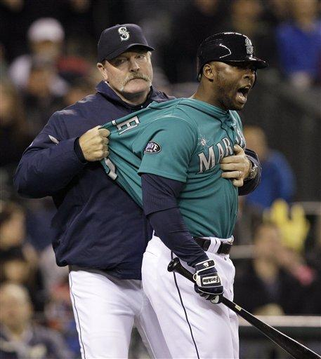 Seattle Mariners manager Eric Wedge, left, pulls Milton Bradley away from umpire Mike Muchlinski after Bradley was called out on strikes against the Chicago White Sox in the eighth inning of a baseball game Friday at Safeco Field. Bradley was ejejected.
