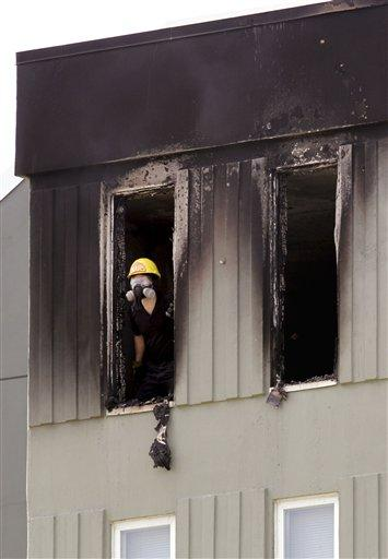 A fire investigator peers out of a charred top-floor apartment where a fire broke out earlier  yesterday (Thurs.) near Seattle's Green Lake. Firefighters quickly doused the 11th floor fire, in the same building as a fatal fire in 2010, adjacent to I-5.