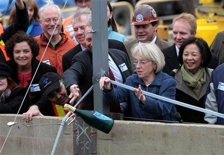 "Sen. Patty Murray drops a ceremonial bottle of ""champagne"" from a zip line to be smashed against a tunnel boring machine several stories below at the University of Washington in Seattle."
