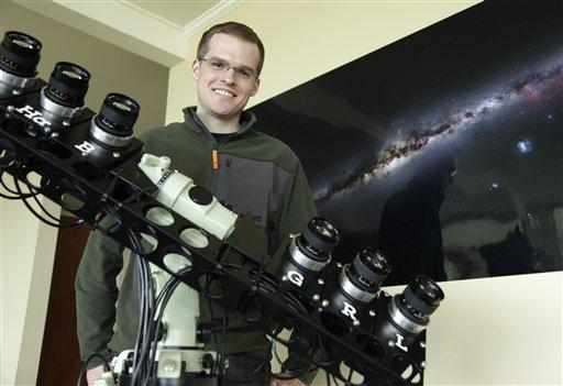 Nick Risinger in Seattle with the rack of six synchronized astrophotography cameras he used to create the photograph on the wall behind him, which shows the entire night sky in a single composite image, made up of more than 37,000 exposures.