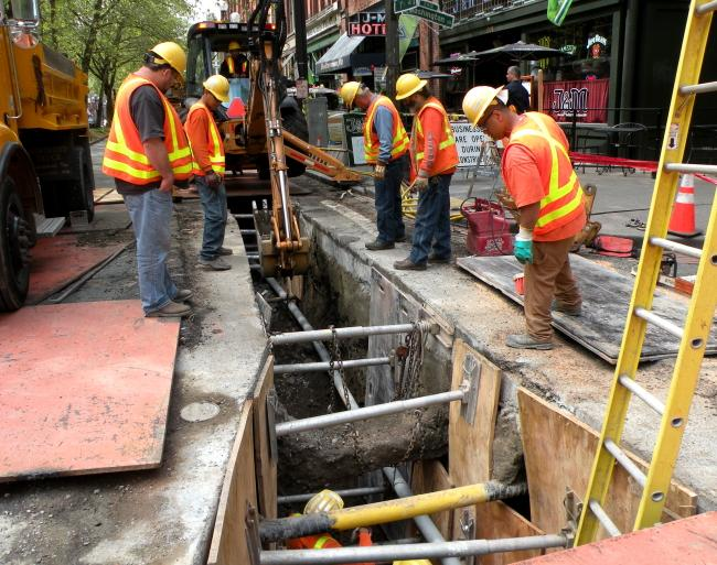 Workers lay conduit under First Avenue South. The pipe belongs to the city, but Mayor Mike McGinn wants to allow private companies to use it to bring faster internet service to small businesses and residential customers.