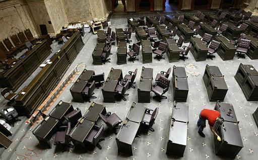 It's all over but the polishing – a worker rubs wood stain into desks on the House Chamber in this file photo. The Washington State Legislature has adjourned after completing a new state budget that fills a projected shortfall of $5 billion.