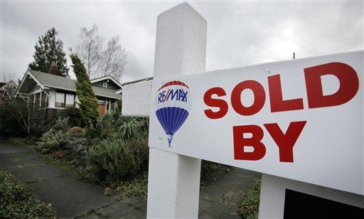 A sign promotes a newly-sold home in Seattle. Home prices continue to fall across most of America's largest cities. Only Seattle and Washington, D.C. bucked the trend.
