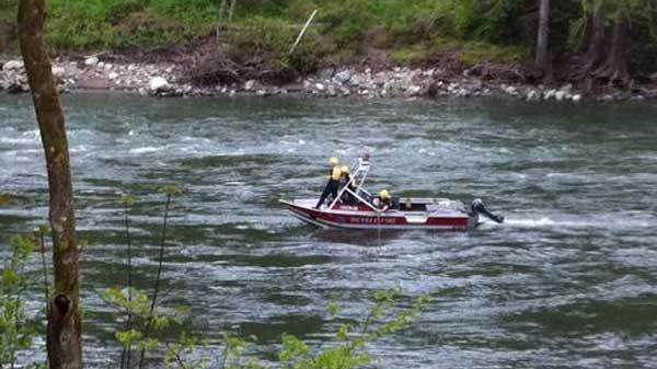 A Duvall fire department boat searches the Snoqualmie River Monday for Johnny Farrar, 28,who has been missing since he jumped into the river on Sunday to rescue a dog.