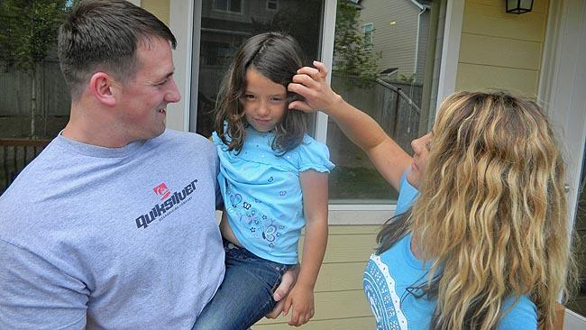 Army Captain Brian Giroux at home in Lacey, Washington with his wife and six-year-old daughter.