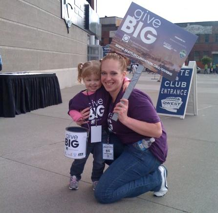 Two fundraising volunteers collecting money for the GiveBIG Challenge at a Seattle Sounder's game at Qwest Field.