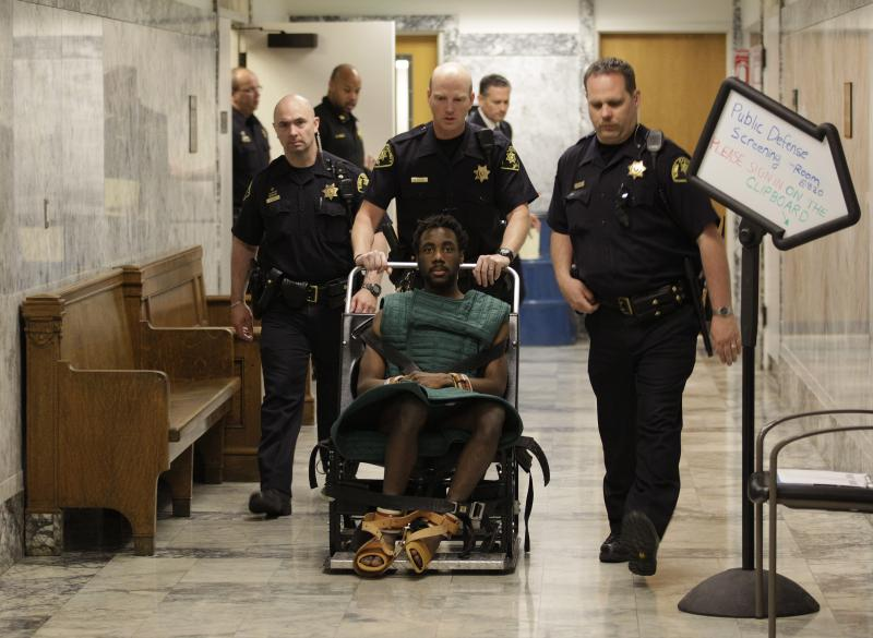 Accused rapist and murderer Isaiah Kalebu is taken in a wheeled restraint chair through a hallway at the King County Courthouse in May. He was not allowed in court Monday, the first day of his trial.