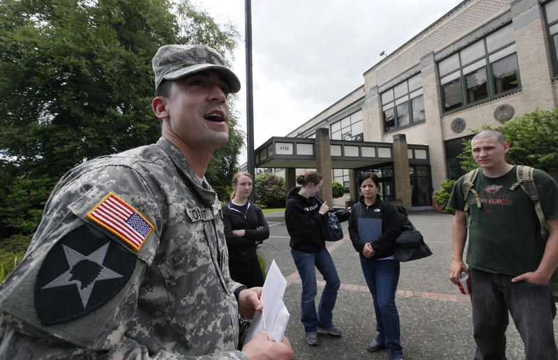 Sgt. Clint Conant, left, stands with potential U.S. Army recruits outside a federal building that houses the Seattle Military Processing Center. Two men have been arrested in a plot to attack on the military recruiting station there.