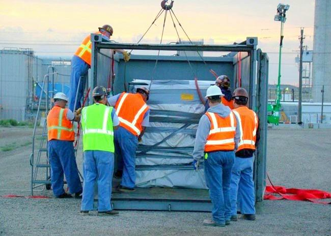Workers secure a box of low level waste for shipment at the Hanford Nuclear Reservation.