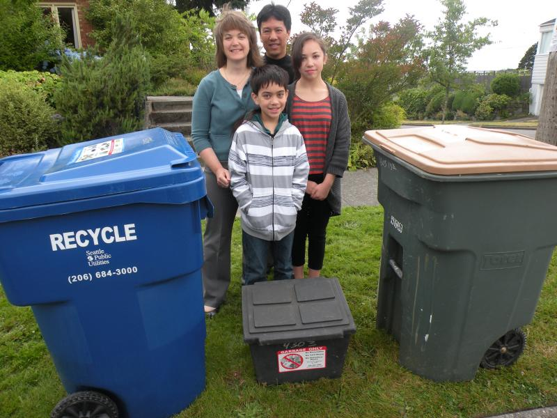 A model Seattle family of recyclers: Bing Tso, Janet Gwilym and their kids put more than 70% of their waste each week into recycling and yard waste bins.  Their trash fits into tiny receptacle at their feet.