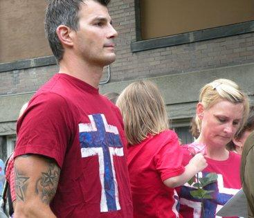 Thomas Cunningham, with his wife Anna and daughter Mia, attend the vigil wearing  Norwegian flag shirts. The t-shirts were made by Anna's mother for the Syttende Mai (Norwegian constitution day) celebration in Ballard in May.