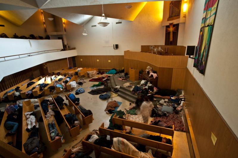 Vancouver, British Columbia, is debating a move to end homelessness. Pictured are many people sleeping in the First United Sanctuary. The Canadian city's plan is similar to one under way in Seattle.