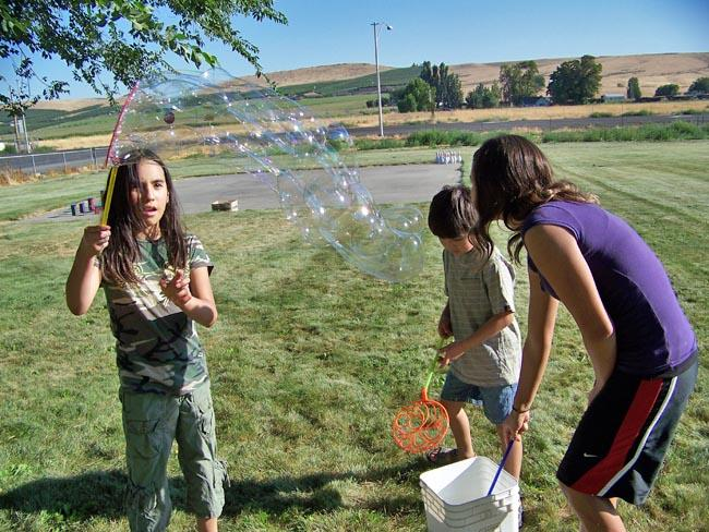 Teresa Rodriguez, 9, left, takes a turn with the bubble wand at a community picnic in Outlook, Wash. The small town is fighting back against gangs with community cleanup days, summer camps for children and educational programs.