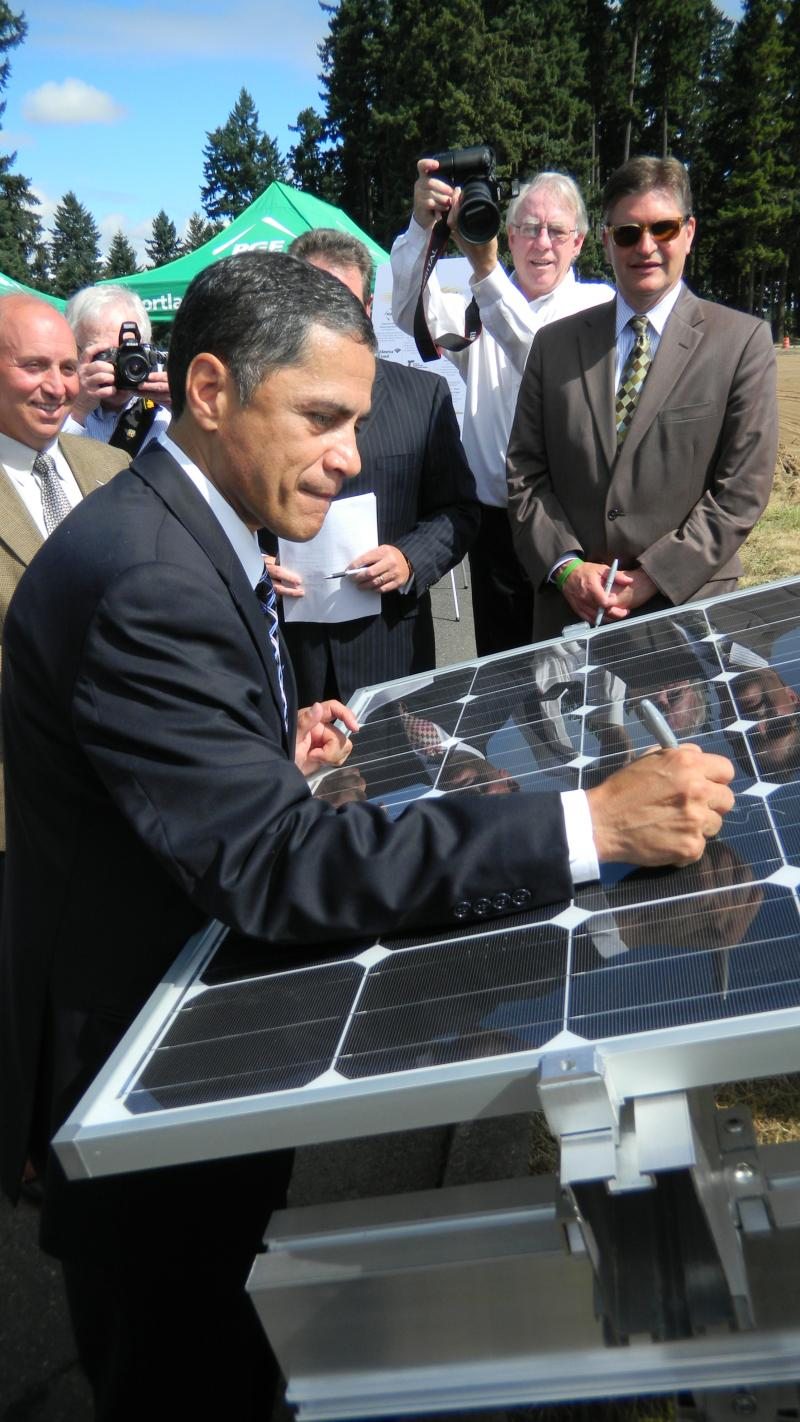 "Federal Highway Administrator Victor Mendez autographs a solar panel at the groundbreaking ceremony for a new ""solar highway"" project along I-5 near Wilsonville, Ore."