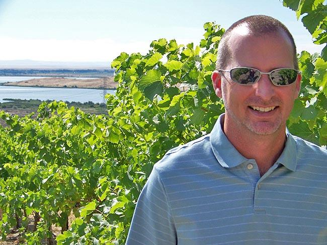 John Derrick, manager, does a check of wine grapes in a vineyard called the Spice Cabinet overlooking the Columbia River.