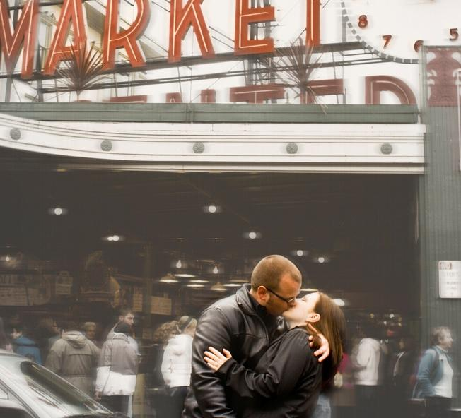 A couple share a kiss in front of Pike Place Market.  Seattle was named the second most promiscuous city by OkCupid.