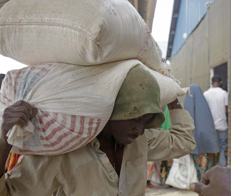 A refugee carries food aid on his back at a food distribution center run by the World Food Programme, in the town of Dadaab, Kenya, today.
