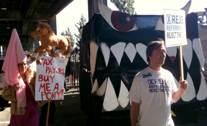 "The protestors carried a 25-foot replica of what they said represented the ""monster tunnel that eats money."""
