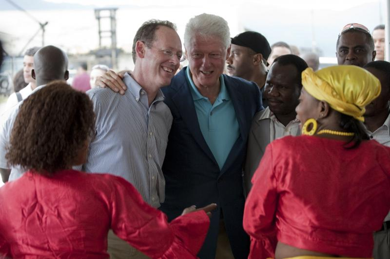 Bill Clinton embraces Paul Farmer, top left, in 2009 as they watch women perform a traditional Haitian dance in Port-au-Prince. In New York on Tuesday, Farmer joined in the clarion call to expand the global health agenda to include all the big killers.