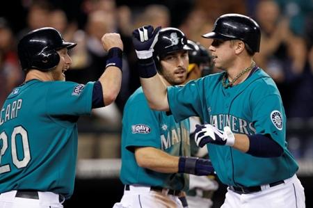 Justin Smoak is met at home by Mike Carp and Dustin Ackley on Smoak's three-run home run against the Oakland Athletics Monday at Safeco Field. They are three of the new faces on the Mariners' roster. Can they help turn things around in 2012?