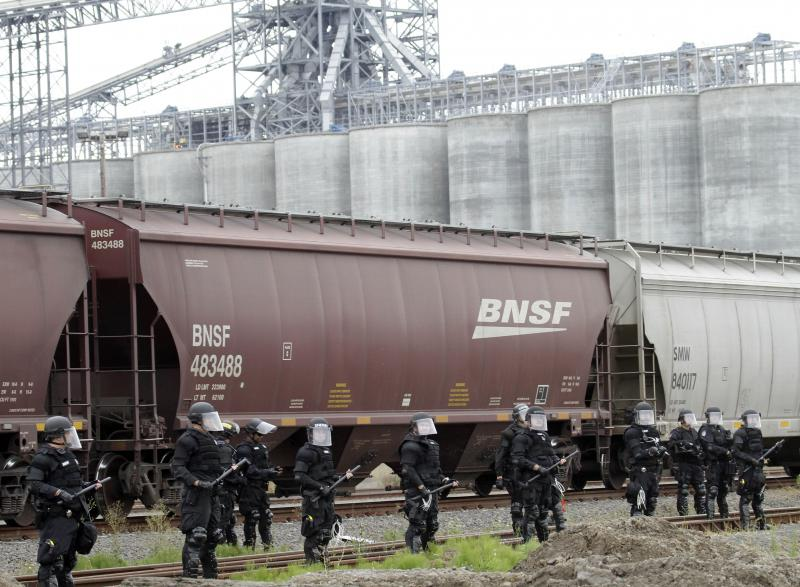 Police in riot gear protect an incoming train carrying grain at the port facilities in Longview, Wash., on Wednesday..