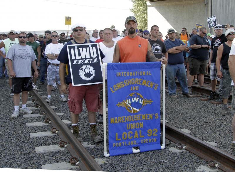 Union workers block railroad tracks in Longview, Wash., Wednesday. Longshoremen blocked a train carrying grain as part of an escalating dispute about labor at the EGT grain terminal at the Port of Longview.