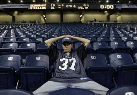 A dejected Seahawks fan sits in the stands after the Hawks lost Super Bowl XL to the Steelers in 2006. The two teams play again on Sunday, with the Hawks 14-point underdogs. KPLU sports commentator Art Thiel calls that a startling spread.