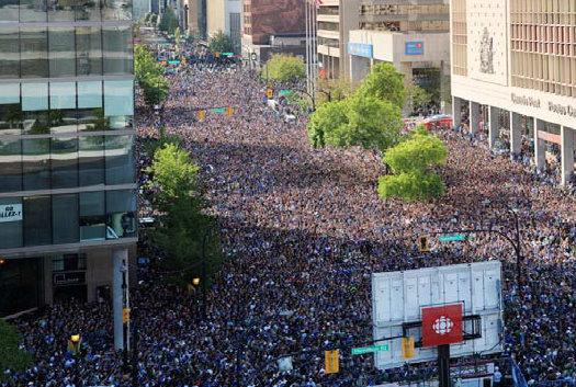 In this image taken from the published review of the Vancouver, B.C., riots, a mass of 155,000 people can be seen gathered to watch the Canucks play the Boston Bruins in the Stanley Cup final. The report says the crowd got too big too fast.