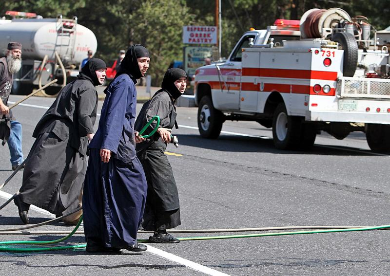 Three sisters from Saint Johns Monastery, about 10 miles east of Goldendale, Wash., race across Highway 97 on Wednesday. The nuns were running garden hoses across the highway to fight the fire and using rags to beat the flames down near the monastery.