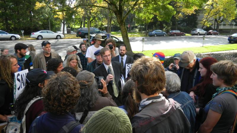 Oregon Treasurer Ted Wheeler speaks with protesters following a meeting of the Oregon Land Board.