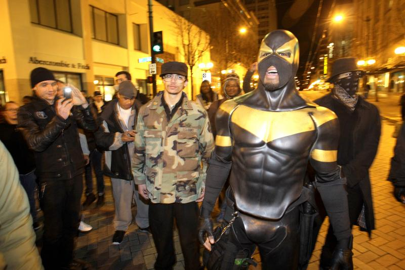 "This February photo, self-styled Seattle superhero ""Phoenix Jones,"" right, in downtown Seattle. Police officers arrested Phoenix Jones early Sunday, Oct. 9, 2011, after he was accused of assaulting several people with pepper spray."