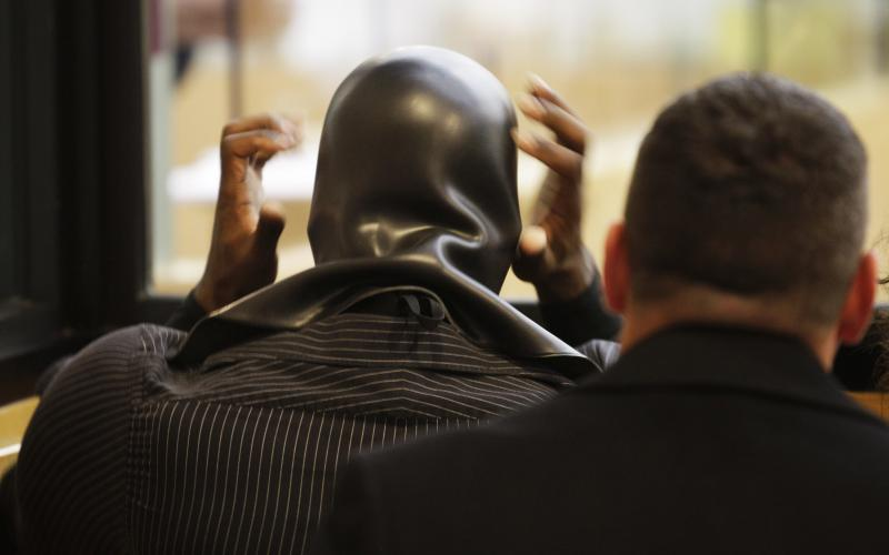 """Ben Fodor, a self-styled superhero who goes by the name """"Phoenix Jones,"""" adjusts his mask after placing it back on his head following a court appearance, on Thursday in Seattle."""