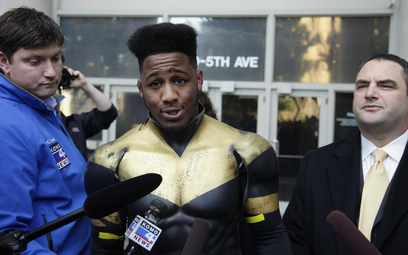 """Ben Fodor, a self-styled superhero who goes by the name """"Phoenix Jones,"""" talks to reporters as he stands next to one of his attorneys, Matt Hartman, right, after Fodor appeared in court on Thursday in Seattle."""