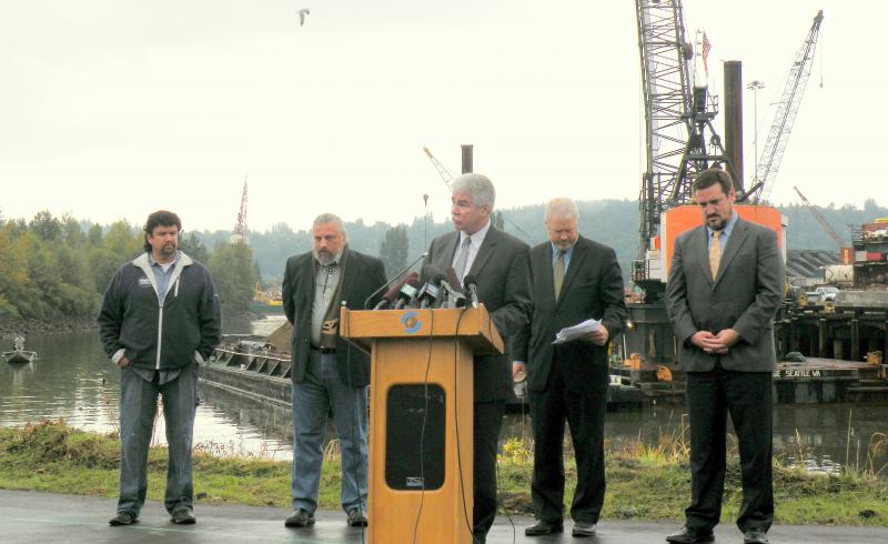 U.S. Environmental Protection Agency Regional Administrator Dennis McLerran celebrates the start of dredging on Slip 4, a hot spot in the Superfund cleanup plan for the Lower Duwamish Waterway.